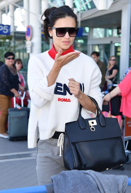 """""""Thiên thần"""" Adriana Lima xuất hiện trẻ trung tại sân bay với túi Studio đen."""